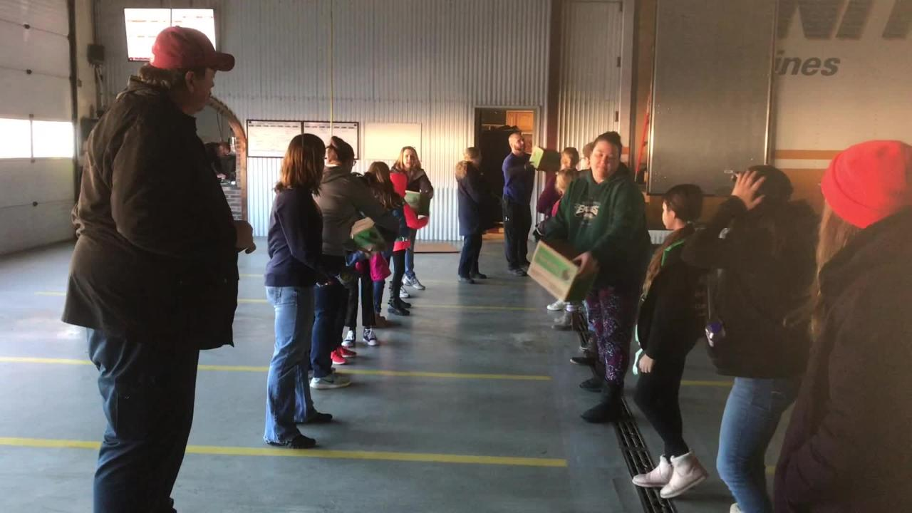 Girl Scouts and their leaders unload thousands of boxes of cookies to deliver to their customers, in Parksley, Virginia on Saturday, Jan. 26, 2019.