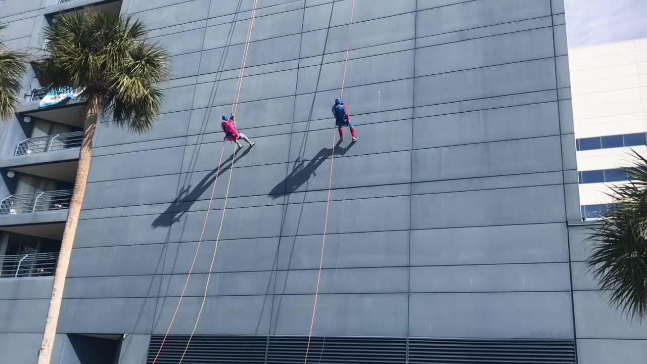 Chef Scott Earick (dressed as Spider-Man) and Suzy Fleming Leonard rappel off Melbourne Hilton Rialto to raise money for Habitat for Humanity.