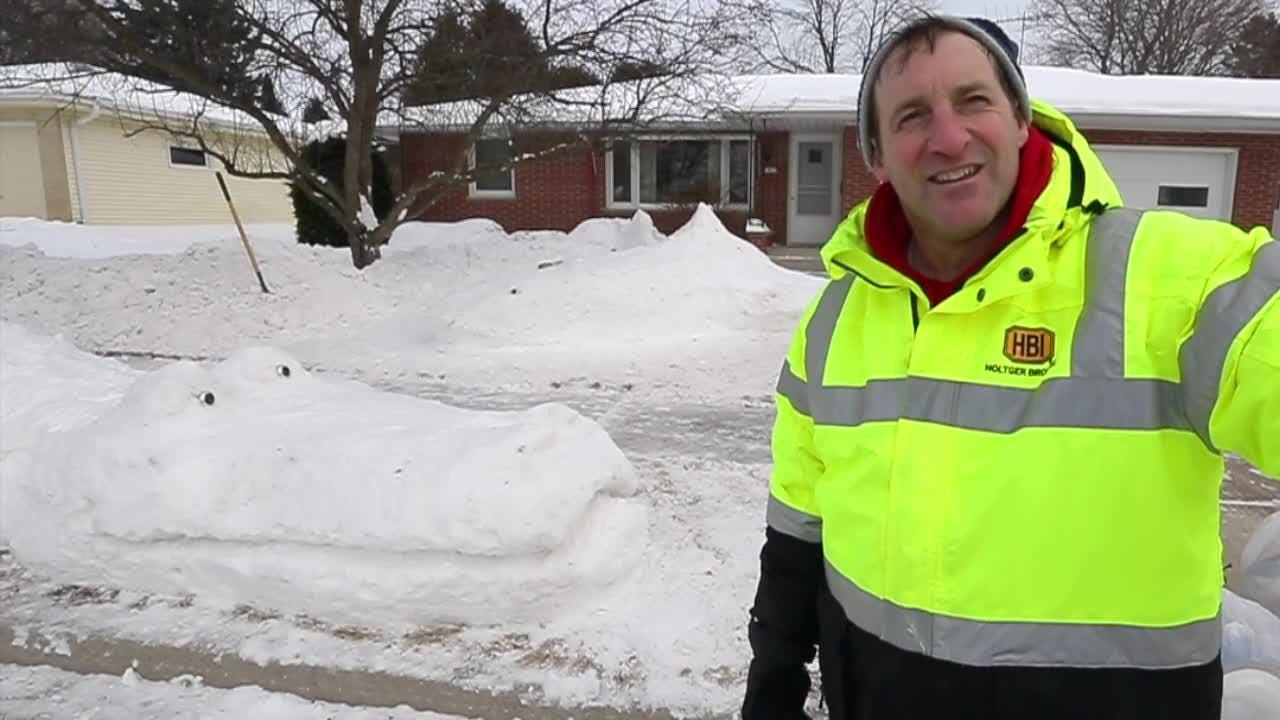 Dennis O' Neill created a whimsical crocodile and shark out of snow in front of his Sheboygan home.
