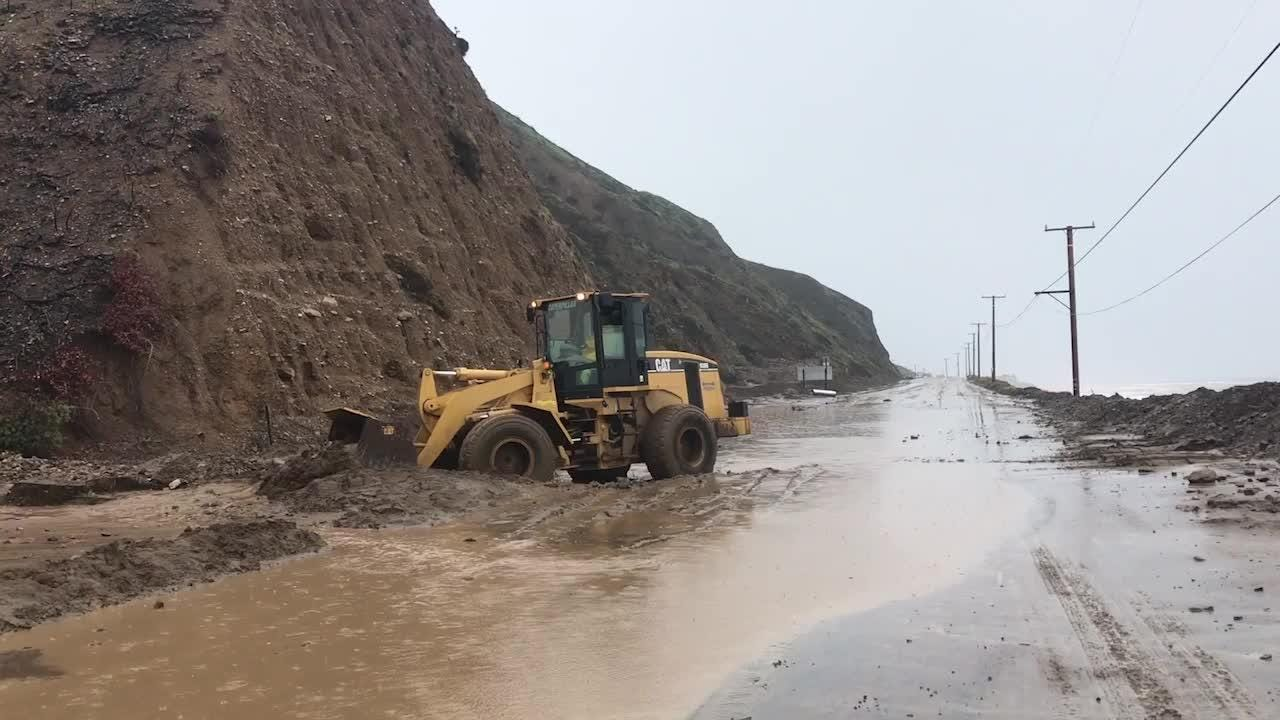 Crews work to clear dirt and rocks off the Pacific Coast Highway near Deer Creek Road after a storm moved through. The debris closed the highway.