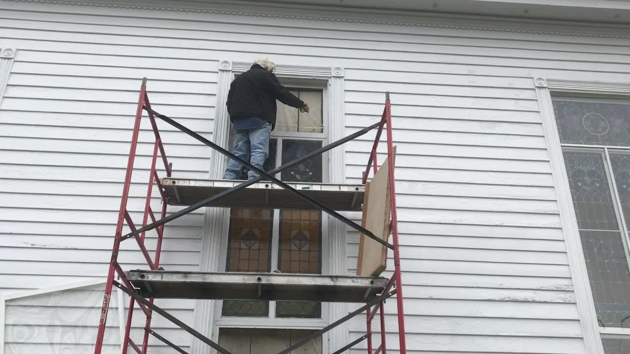 Michael Mezalick measures a stained glass window at Historic Cokesbury Church in Onancock, Virginia that is undergoing restoration, on Monday, Jan. 28, 2019.