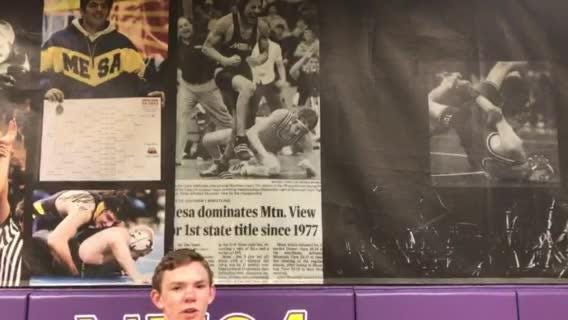 Mesa senior Steve Jarman talks his brother Tim Jarman's state wrestling title profiled in Arizona Republic posted on the Mesa practice room wall.