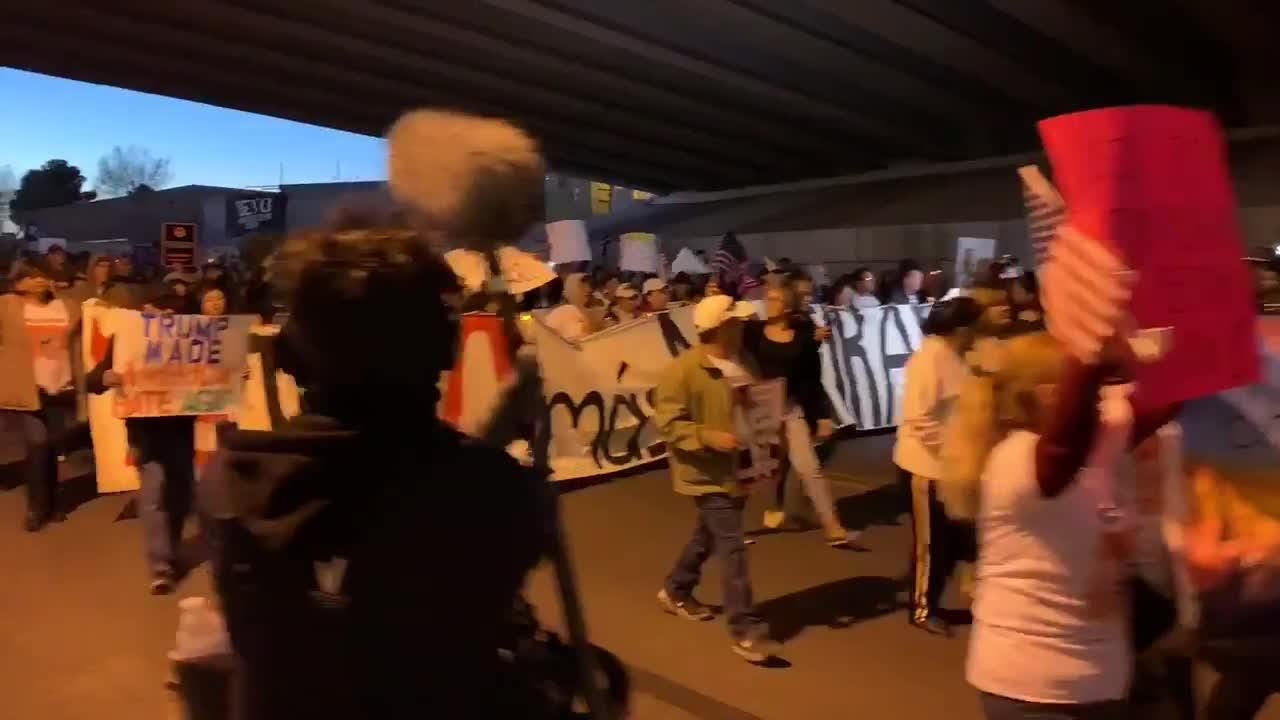 Hundreds march together under a freeway overpass along the border fence separating El Paso from Ciudad Juarez on February 11, 2018.