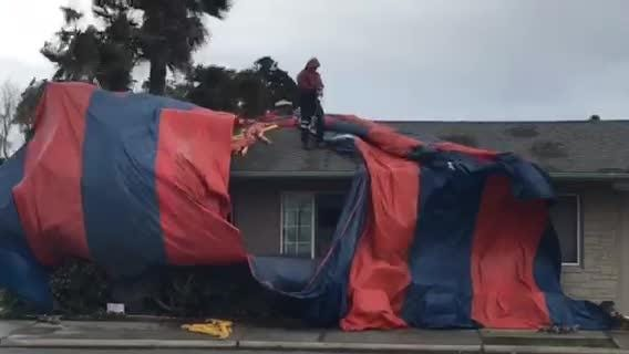 Workers struggled to pull down tarps after fumigating at the Economy Inn at California and John streets.