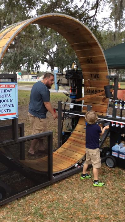 Yitzi Baum, one of the owners of You Are The Hamster, and his son, James, demonstrate how to make a snow cone with their giant hamster wheel.