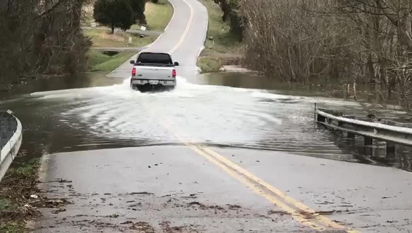 A truck passes through high water on Chapel Hill Road at Hurricane Creek Bridge on Friday, Feb. 22, 2019. He made it, but emergency officials have to rescue people every year who don't.