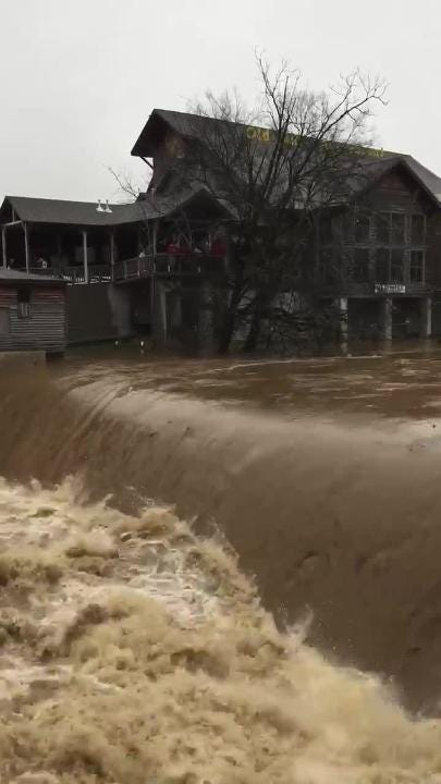 Flood waters race past The Old Mill Restaurant in Pigeon Forge. East Tennessee has been dealing with rock slides and flood waters for the last couple days.