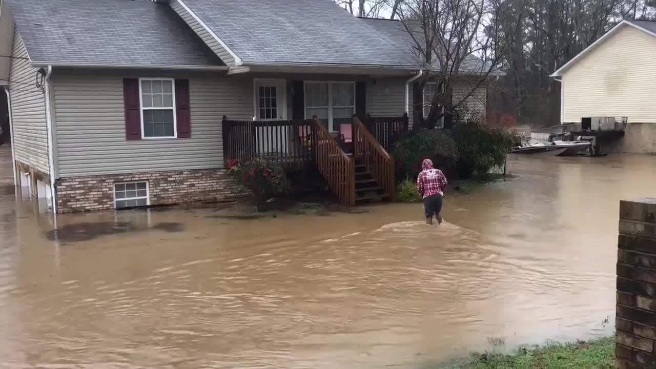 """Payne School Road resident identified as """"Dee"""" wades to her front steps to """"grab a few things"""" before being evacuated."""