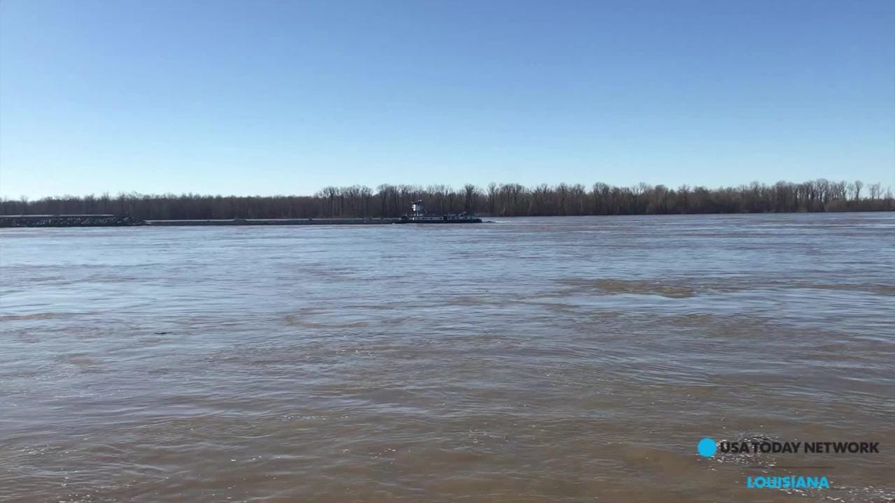 A barge navigates the flooded Mississippi River Sunday at Vicksburg, Miss.