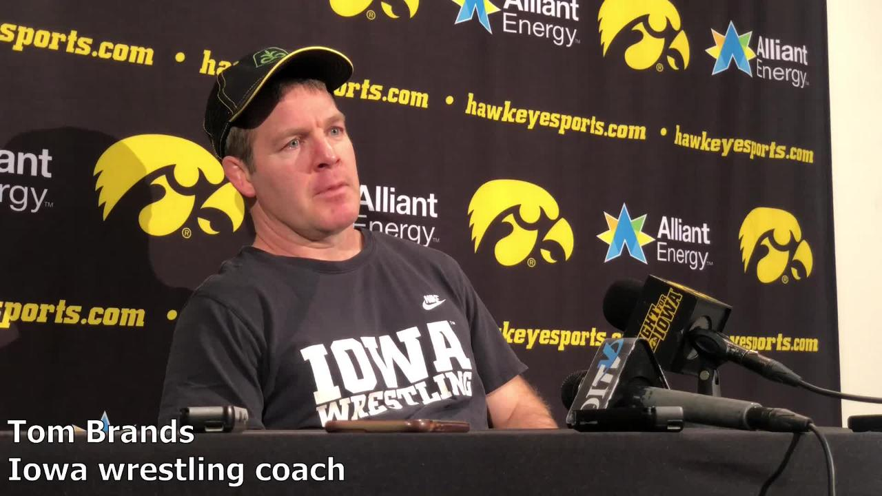 Iowa wrestling coach Tom Brands offers his congratulations to Reese Morgan, who retired after 19 years as an assistant coach for the Iowa football program on Wednesday.