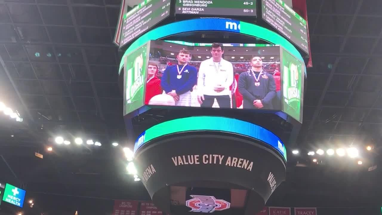 The Schottenstein Center shows Northmor junior Conor Becker receiving his state title medal after winning at DIII 170 with a second period pin.