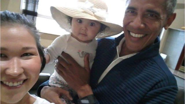 """A mother in Alaska is cherishing cellphone photos she snapped of her wide-eyed 6-month-old baby in the arms of former President Barack Obama. Jolene Jackinsky was at Anchorage International Airport on Monday looking for an airline when she ended up in a waiting area for private flights where a man she thought looked like Obama was sitting. She said, """"I think it's unreal and pretty exciting that I get to have a picture with him and my baby. Not a lot of people get to meet him."""""""