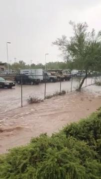 Floodwaters race past the Apache Junction Police Department. Robert E. Wheeler Jr./Special for azcentral.com