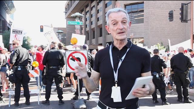 Columnist EJ Montini broadcasts among the protesters at President Trump's Phoenix rally.