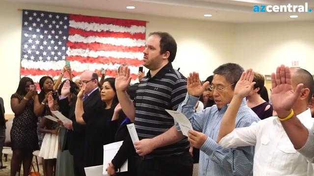 New citizens watch a video message from President Donald Trump and celebrate their new nationality Oct. 24, 2017, at the U.S. Citizenship and Immigration Services office in Phoenix.