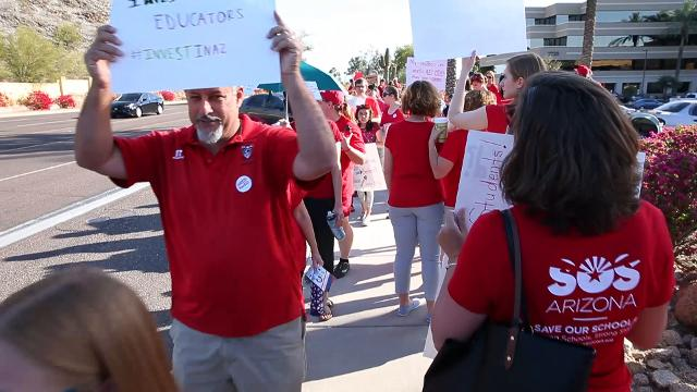 Teachers and supporters protest outside the KTAR studios where Gov. Doug Ducey was a guest. Michael Chow/azcentral.com