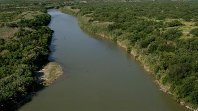 USA Today Network reporter Dennis Wagner reports on the terrain along the Rio Grande River in Texas during a low altitude flight in a helicopter.