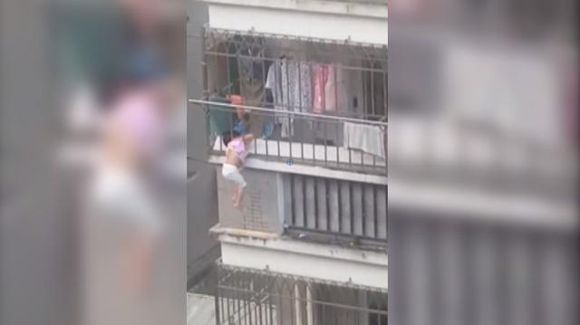 Girl's head gets trapped, she dangles from balcony