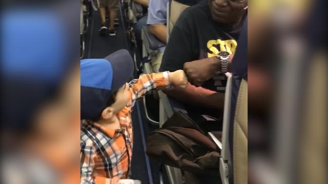 Toddler makes passengers smile with adorable fist bumps