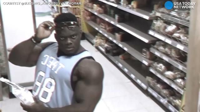 Bodybuilder flexes for surveillance camera