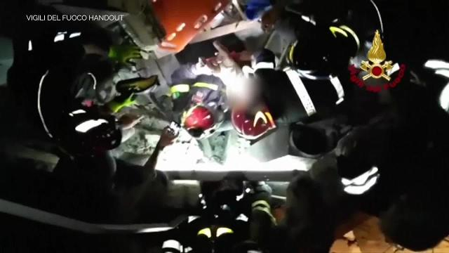 Firefighters rescue an infant from earthquake rubble in Italy