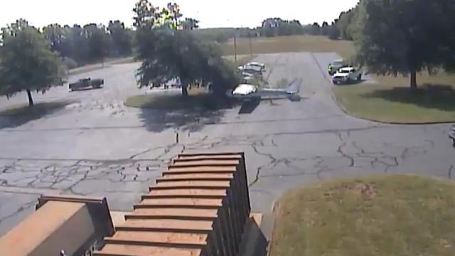 Plane crashes into tree, flips into parking lot