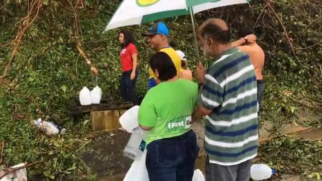 Raw: Puerto Ricans assess damage, collect water
