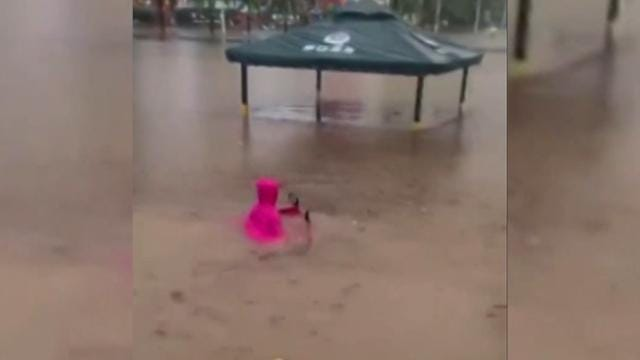 This woman riding her scooter through elbow-deep floodwater in southern China is a realistic portrayal of us trying to make it to Friday.