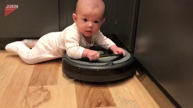 Baby and robotic vacuum join forces