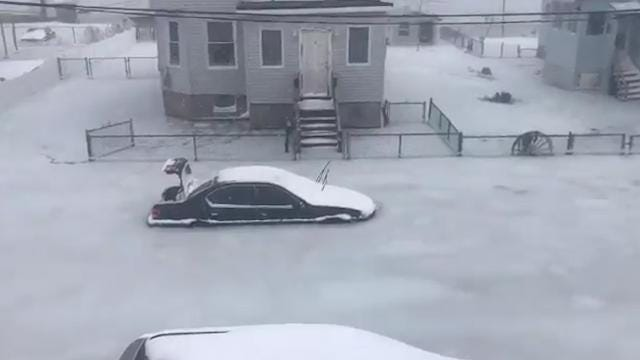 """That's not just snow. Floodwaters froze over and trapped cars as the """"bomb cyclone"""" pushed through Revere, Massachusetts."""