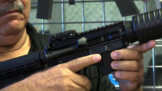 Florida gun shop owner displays a semi-automatic rifle.