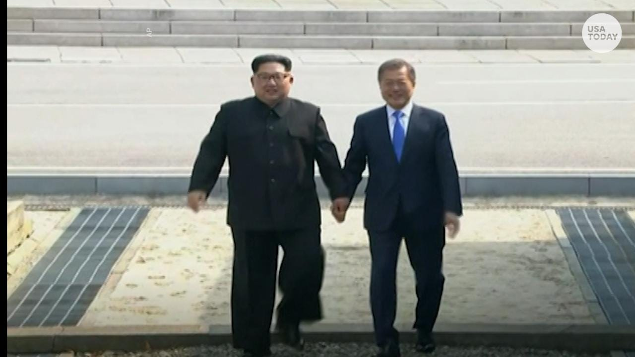 North and South Korea leaders hold hands after arriving for a historic summit between the two countries.