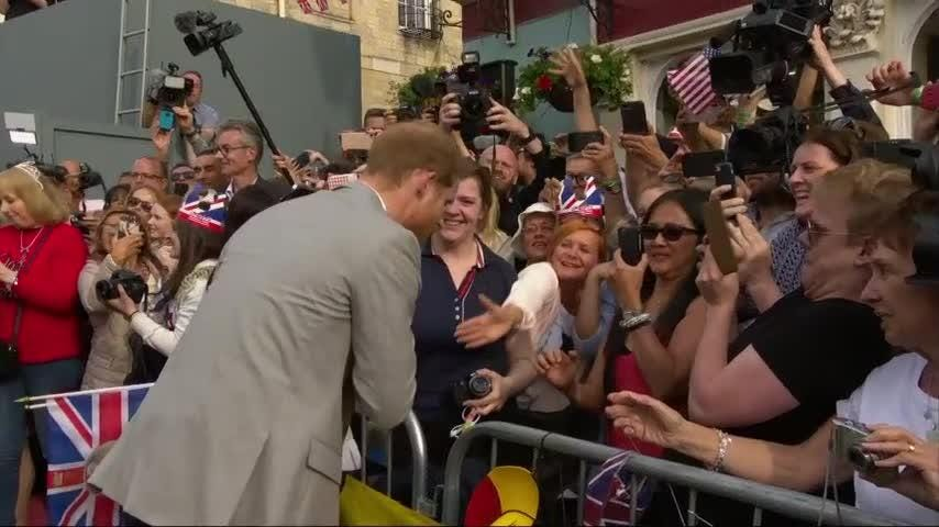 Prince Harry and his best-man brother Prince William greet some of the thousands of well-wishers gathered outside Windsor Castle for the royal wedding.
