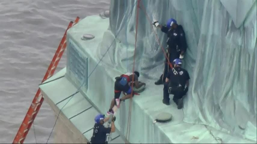 statue of liberty person climbs statue after abolish ice protest