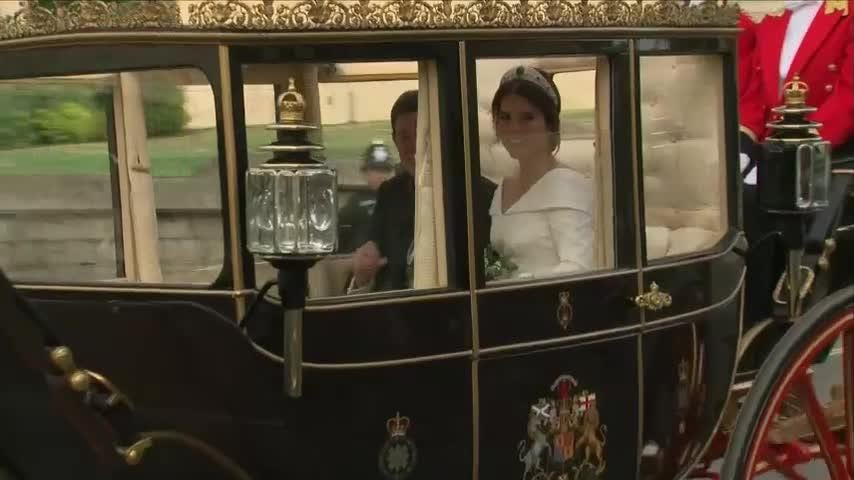 Newlyweds Princess Eugenie and Jack Brooksbank depart St. George's Chapel in carriage through Windsor, as the royal family looks on. (Oct. 12)
