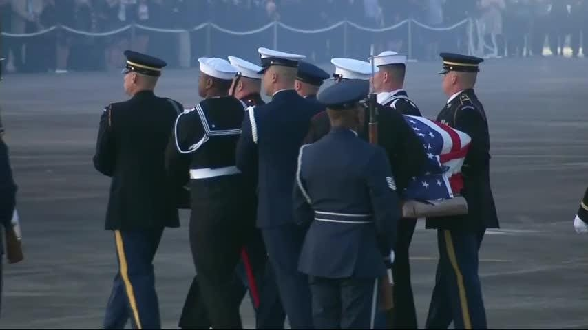 A military band played and guns and cannons were fired symbolically as the body of George H.W. Bush was taken from a military aircraft to a waiting hearse in Houston. (Dec. 5)