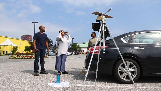 Paul Funches, left, Nikki Stars, center, and Idris Hayward view the eclipse from the parking lot of Joe's Crab Shack in Wilmington.
