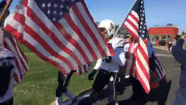 Delaware Military Academy marches with flags to face Conrad