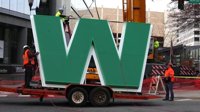 Workers hoisted the lettering above WSFS Bank's downtown Wilmington headquarters Saturday as the bank updates its look. A crane lifted the signage in place; the new version will be larger with improved lighting.