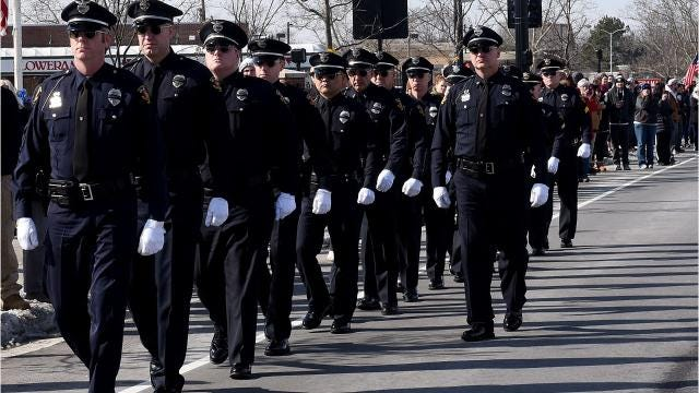 State Street in Westerville is lined with people as the procession for fallen Westerville police officers Eric Joering and Anthony Morelli comes to a stop in front of Hill Funeral Home Monday afternoon