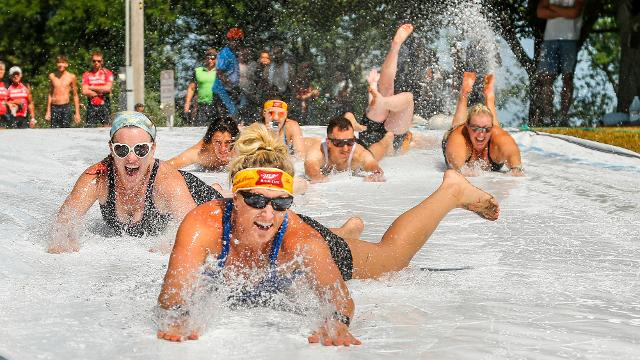 RAGBRAI riders cool off in on a slip and slide outside Paullina.