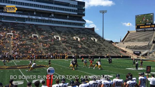 Bo Bower runs over Toks Akinibade at Iowa's Kids Day open practice