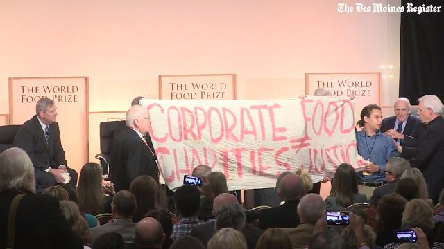 Watch as protesters are escorted out of the room after carrying a sign into the World Food Prize's Iowa Hunger summit featuring a panel with the five previous U.S. Secretaries of Agriculture.