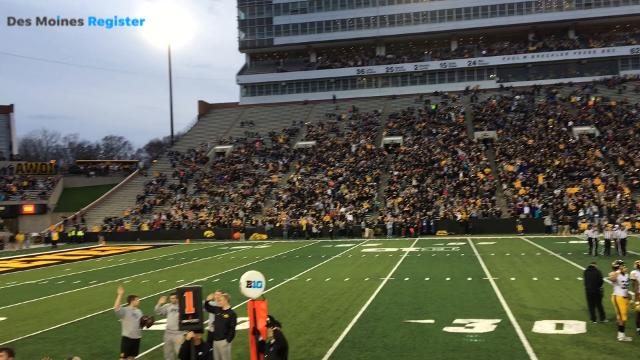 Fans and players at Kinnick Stadium do the Hawkeye Wave during Iowa football's open practice on Friday.