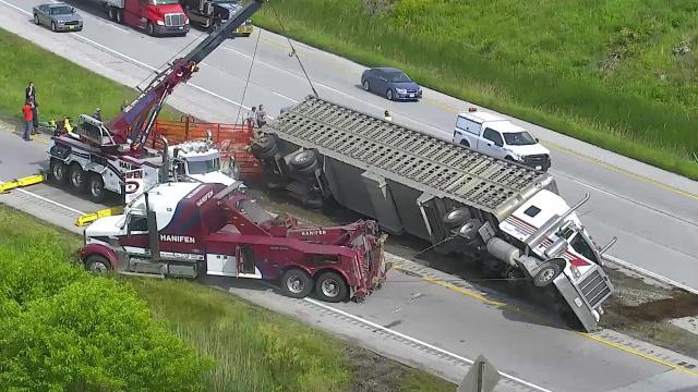 Traffic camera video provided by the Iowa DOT shows the scene of a overturned semitrailer and the efforts to save nearly 200 hogs on board.