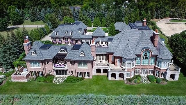 This house is so large, with so many extensions, that on one side, its wings enclose a large motor court, and on another side, more wings wrap a long, glamorous pool.
