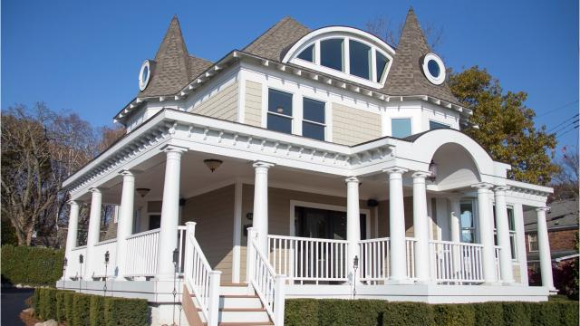 At first glance you know this house is Victorian — the steep witches-hat roofs, the wide porch, the stacked bay windows. On second look you see someone's having fun with the 1896 house.