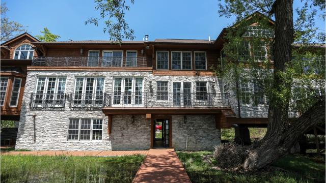 Unusual luxury house is built on 60-foot deep piers at the edge of Orchard Lake, 350 feet of shoreline.