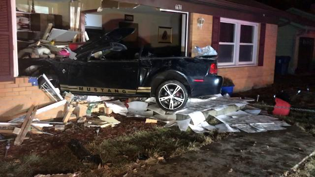 Wayne Township firefighters respond after a car drove into a home on Friday, Feb. 10, 2018, on the west side of Indianapolis near Farley Drive and Doris Drive.