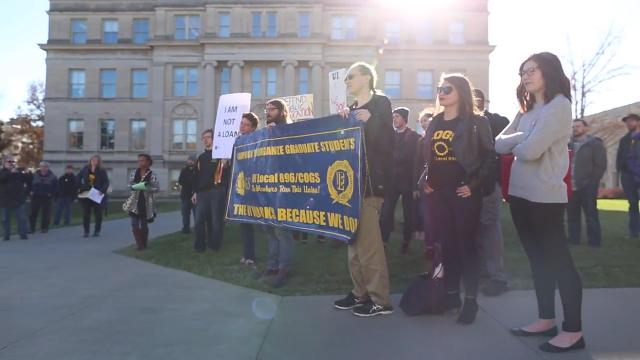 Protesters gathered on the Pentacrest this afternoon for a rally against the graduate student tax.